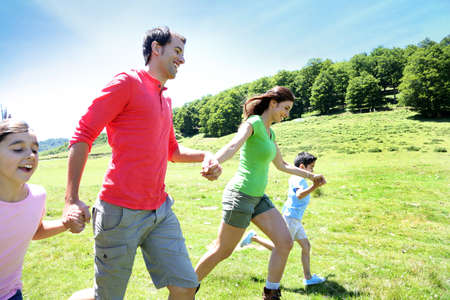 Happy family enjoying and running together in the mountains Stock Photo - 14663698