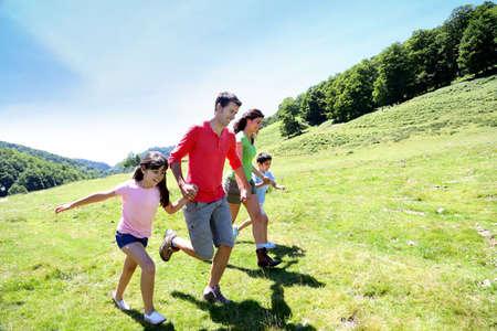 Famiglia felice godendo e in esecuzione insieme in montagna photo