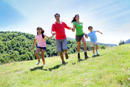 Happy family enjoying and running together in the mountains Stock Photo - 14663710