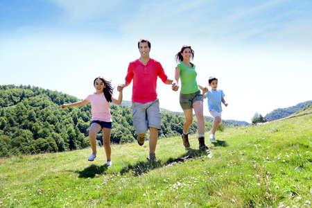 幸せな家族を楽しむと山で一緒に実行します。 写真素材