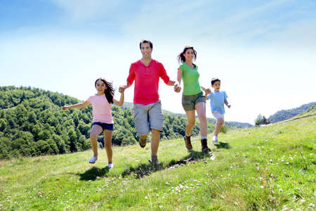 four people: Happy family enjoying and running together in the mountains