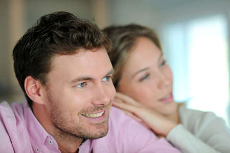 Portrait of smiling couple relaxing at home photo