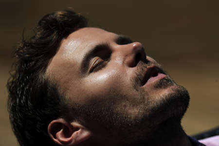 sleeping face: Man laying on long chiar taking the sun