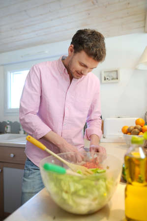 Man at home preparing salad for dinner photo