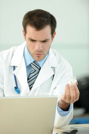 medicalcare: Closeup of doctor holding pills in front of laptop Stock Photo