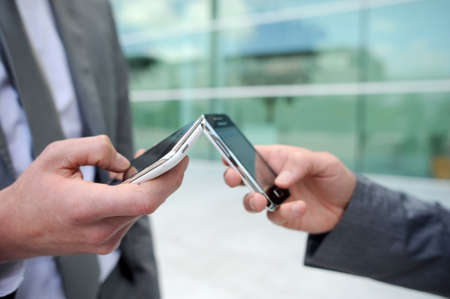 exchanging: Closeup on mobile phones hold by business people
