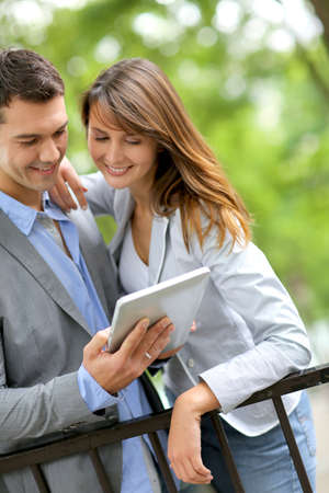 Couple standing in park with electronic tablet Stock Photo - 14663814