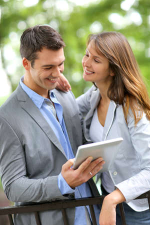 Couple standing in park with electronic tablet photo
