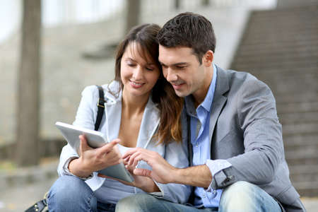 electronic tablet: Cheerful couple sitting in stairs with electronic tablet Stock Photo