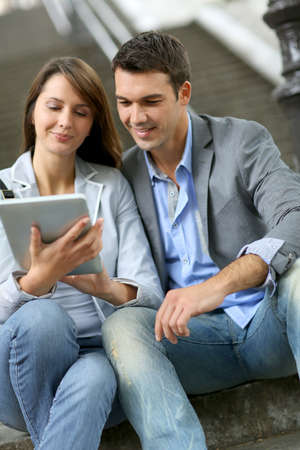 Cheerful couple sitting in stairs with electronic tablet Stock Photo - 14663821