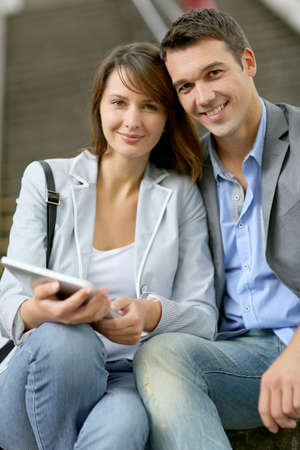 Cheerful couple sitting in stairs with electronic tablet photo