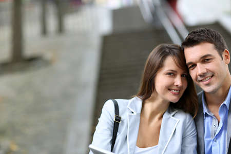 Cheerful couple sitting in stairs with electronic tablet Stock Photo - 14663764
