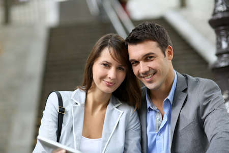 Cheerful couple sitting in stairs with electronic tablet Stock Photo - 14663817