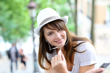 Trendy young woman using smartphone in public park photo