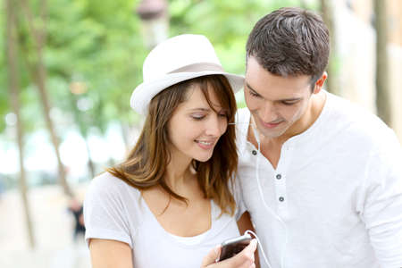 handsfree device: Couple in town using smartphone and handsfree device