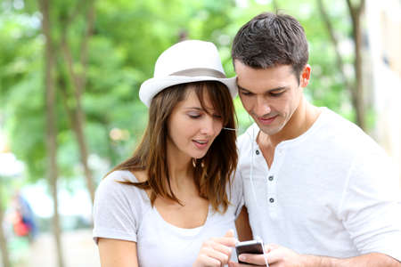 Couple in town using smartphone and handsfree device photo