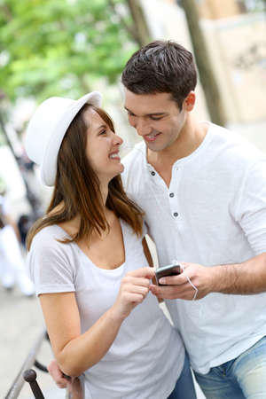 foreign: Couple in town using smartphone and handsfree device