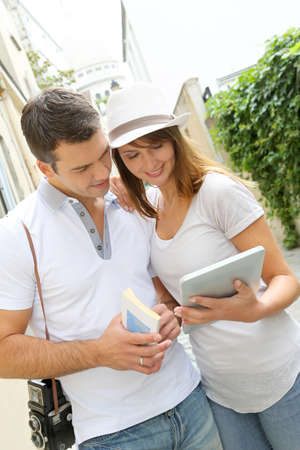 guide book: Couple of tourists using guide and tablet in town