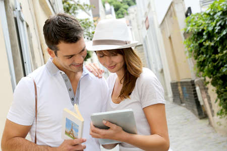 Couple of tourists using guide and tablet in town photo
