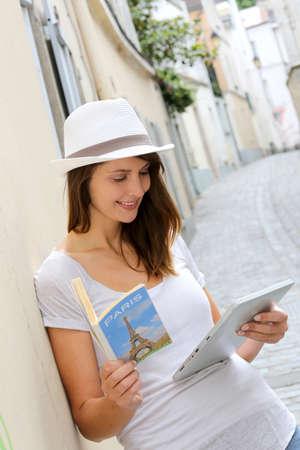 tour guide: Mujer en la calle de Par�s mirando gu�a tur�stica Foto de archivo