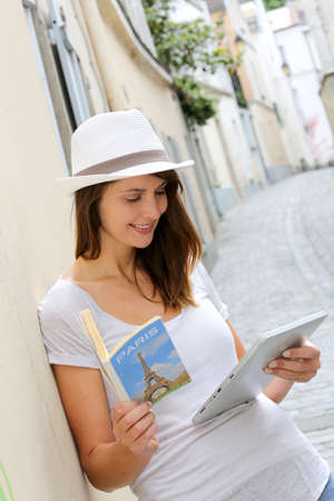 Woman in the street of Paris looking at tourist guide Фото со стока