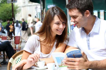 tour guide: Pareja en una tienda de caf� libro tur�stica terraza de lectura Foto de archivo