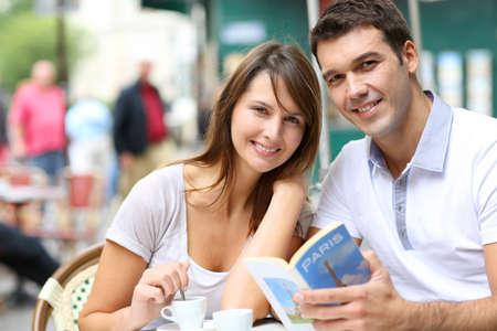 Couple on a coffee shop terrace reading tourist book Фото со стока