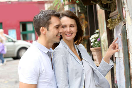 Couple in Paris looking at restaurant menu photo