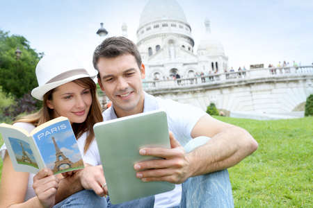 travel guide: Couple using tablet in front of Sacre Coeur Basilica