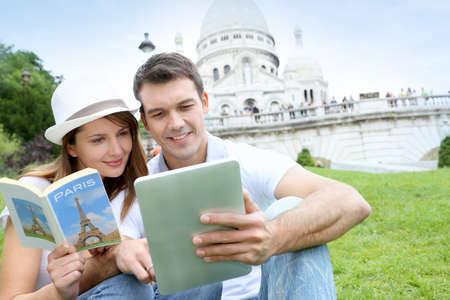 coeur: Echtpaar met behulp van tablet in de voorkant van Basilique du Sacre Coeur Stockfoto