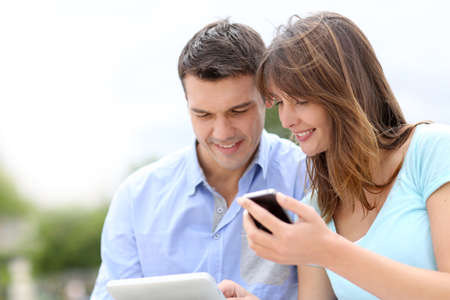 electronic tablet: Couple using tablet and cellphone in public park Stock Photo