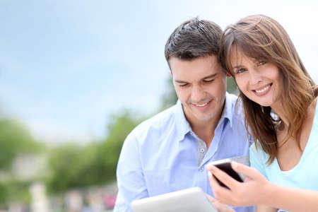 public park: Parejas que usa la tableta y el tel�fono celular en parque p�blico