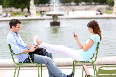 Couple relaxing in chairs in public park Stock Photo - 14663797