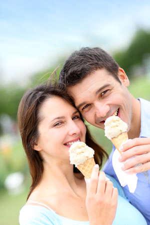 eating ice cream: Pareja en el parque comiendo conos de helado Foto de archivo