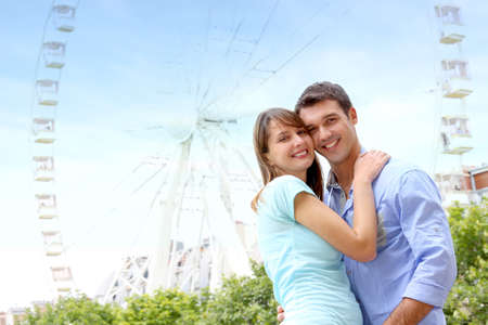 Romantic couple embracing in front of the Ferris Wheel photo