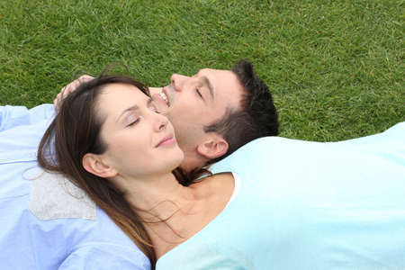 eyes shut: Top view of couple relaxing with eyes shut in grass Stock Photo