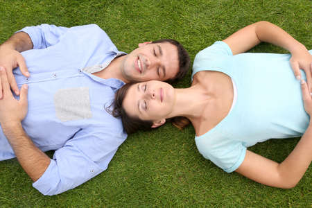 Top view of couple relaxing with eyes shut in grass photo