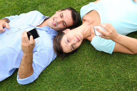 Couple relaxing in grass while using smartphone photo