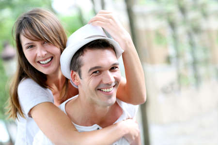 shoulder ride: Man carrying girlfriend on his back in public park Stock Photo