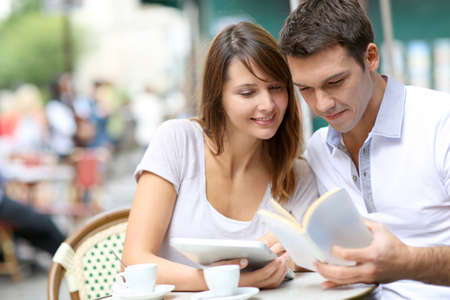 Couple on a coffee shop terrace reading tourist book Stock Photo