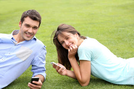 Couple using smartphone laying in public park photo