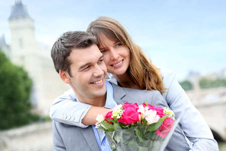 engagements: Portrait of romantic man giving flowers to woman Stock Photo
