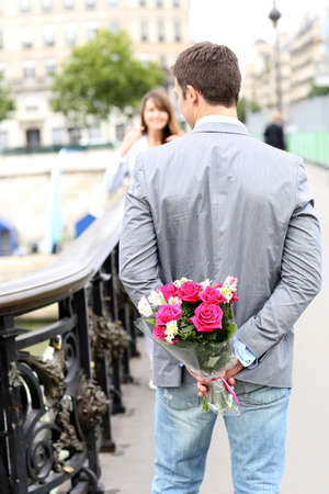 declaration: Man ready to give flowers to girlfriend on a bridge Stock Photo