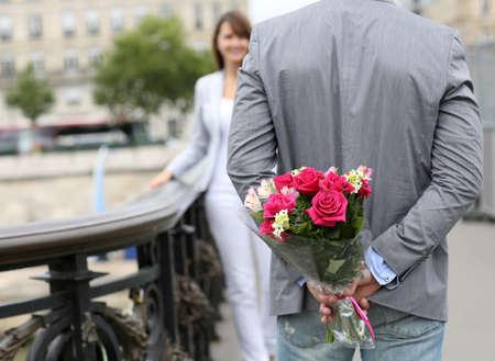 simbolo uomo donna: L'uomo pronto a dare fiori alla fidanzata su un ponte