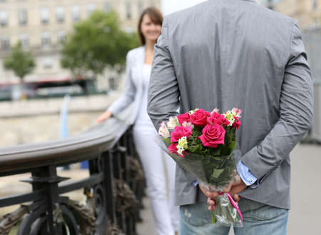 declaration of love: Man ready to give flowers to girlfriend on a bridge Stock Photo