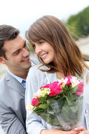 Portrait of romantic man giving flowers to woman Zdjęcie Seryjne