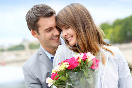 anniversary flower: Portrait of romantic man giving flowers to woman Stock Photo