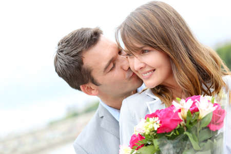 offering: Portrait of romantic man giving flowers to woman Stock Photo