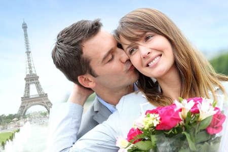 baiser amoureux: Homme donnant des fleurs � la femme � Paris de la Tour Eiffel