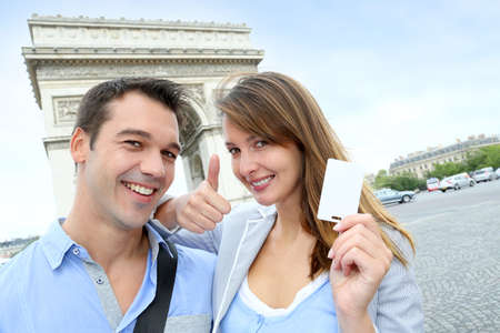 Cheerful couple holding tourist ticket by the Arch of Triumph photo
